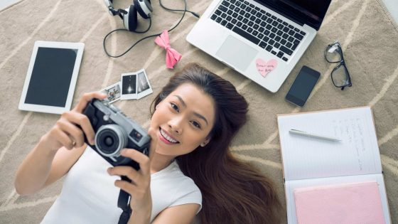 With Builder Cheerful Vietnamese girl lying on the floor with her camera in hands 560x315